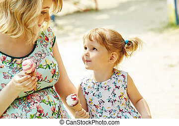 Mom and child eating ice cream. mother and daughter outdoors.