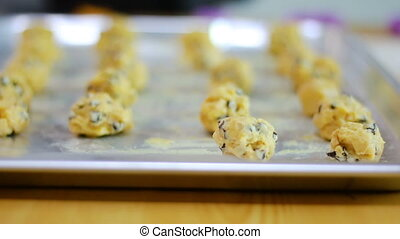 Mom and child hands are preparing and arranging cookie dough...