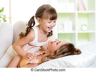 Mom and child having fun in bed - Happy mom and child girl...