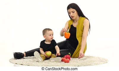 Mom and child in a spacious room and look at vegetables....