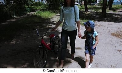 Mom and child roll a bicycle
