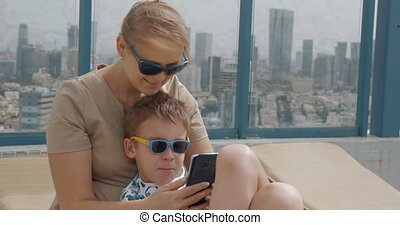 Mom and child using mobile when relaxing on hotel rooftop in...