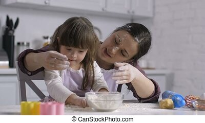 Mom and child with down syndrome playing with flour -...