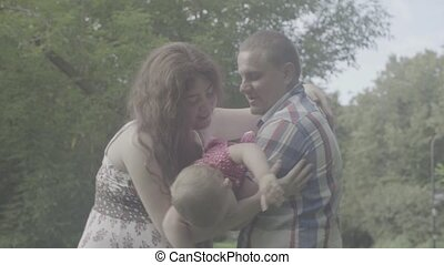 Mom and dad holding baby and swinging her