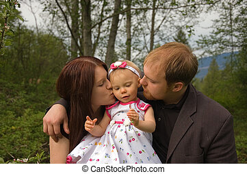 Mom and Dad Kissing Toddler