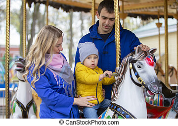 Mom and dad with the baby on the carousel.Family resting in the park.Parents with a little son