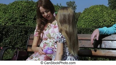A pregnant mom and daughter sit on a bench and play with baby booties