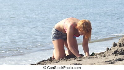 Mom and daughter are building a sand castle