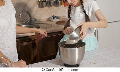 Mom and daughter are cooking a sponge cake together in the...