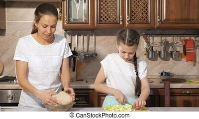 Mom and daughter are cooking apple pie together in the...