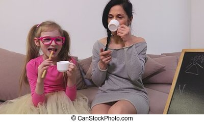 Mom and daughter are joking, eat and drink on sofa