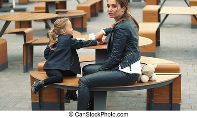 mom and daughter are sitting at the table