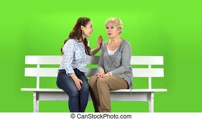 Mom and daughter are sitting on a bench. Green screen