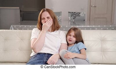 Mom and daughter are sitting on the couch, they both yawn and want to sleep. family evening screening of the film. contagious yawning.