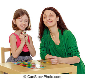 Mom and daughter at the table playing educational games -...