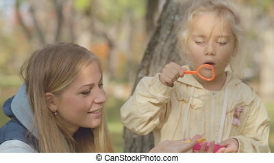 Mom and daughter blow bubbles in the park