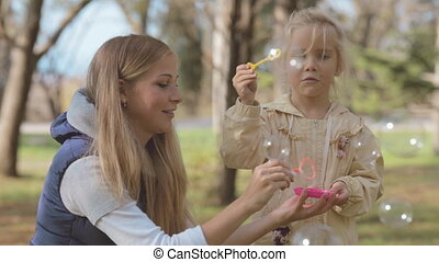 Mom and daughter blowing bubbles in the park