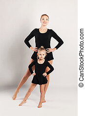 Mom teaching her daughter dancing on white background. family sports