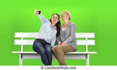 Mom and daughter do selfie. Green screen