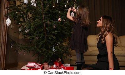 Mom and daughter dress up a Christmas tree on Christmas Eve