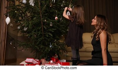 Mom and daughter dress up a Christmas tree on Christmas Eve