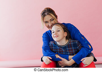Mom and daughter family cuddling on pink background