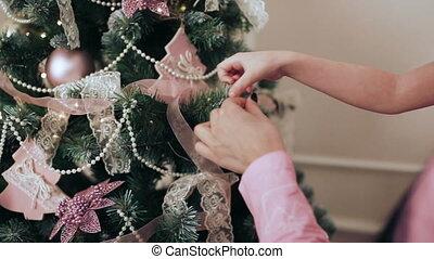 Mom and daughter hang a ball on a Christmas tree