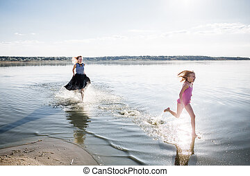 Mom and daughter have fun and run on the water. The state of happiness, freedom and independence. Strengthening parent-child relationships, as well as physical and psychological health in the family..