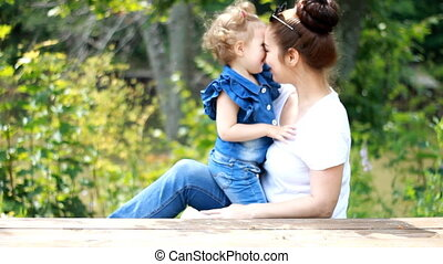 Mom and daughter hug and kiss in the park.