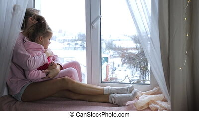 Mom and daughter hug, sitting on the windowsill and look out...