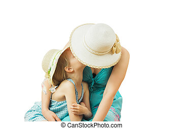 Mom and daughter in hats embracing on the floor isolated on white background.