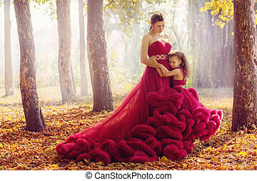 Mom and daughter in luxurious dresses