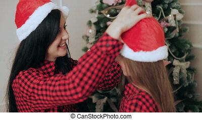 Mom and daughter in santa hats hugging near Christmas tree