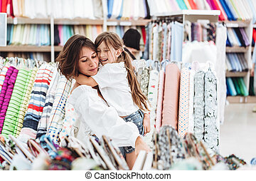 Mom and daughter in the fabric store choose fabric - Mom and...