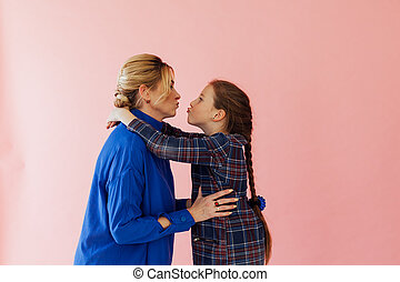 Mom and daughter laugh and kiss on a pink background