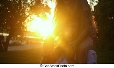 Mom and daughter laugh merrily at sunset. Daughter sits on mom's shoulders and laughs during an evening walk in the city park. The concept of a happy family. Slow motion.