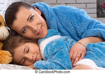 Mom and daughter lie in bed