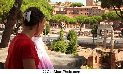 Mom and daughter looking at the city from above, ruins of...