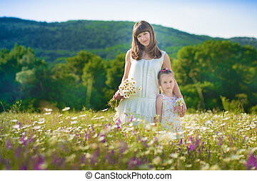 Mom and daughter on a picnic in the chamomile field. Two beautiful blondes in chamomile field on a background of horse. Mother and daughter embracing in the chamomile field