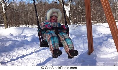 Mom and daughter on a swing - In winter park girl with mom...
