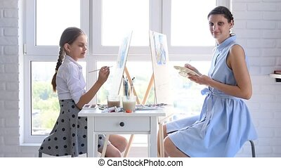Mom and daughter paint at home in front of the window on easels and looked into the frame