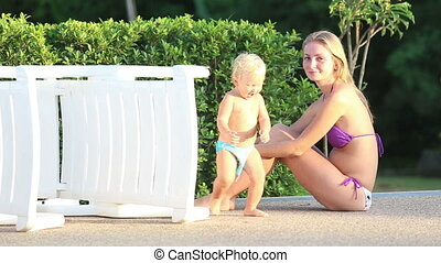 mom and daughter play in the pool