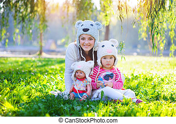 Mom and daughter playing in the park with a doll