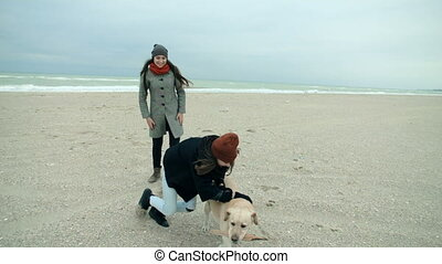 Mom and daughter playing on the beach with a dog.