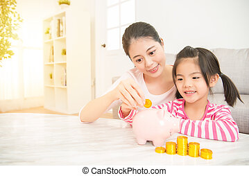 mom and daughter putting coins into piggy bank