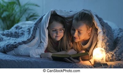 Mom and daughter reading book in bed under blanket