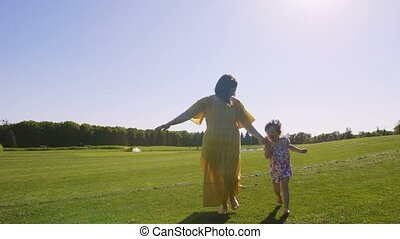 Mom and daughter running together on meadow