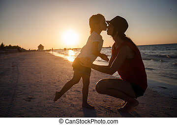 Mom and daughter silhouette in the sunset at the beach on Holbox island