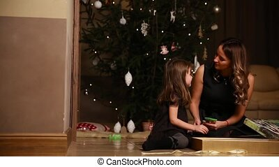 Mom and daughter sitting under the Christmas tree open gifts. A girl untying a gift ribbon