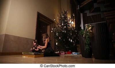 Mom and daughter sitting under the Christmas tree open...